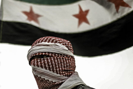 Syria Independence Flag behind a Free Syrian Army member by FreedomHouse2 under a cc license from Flickr