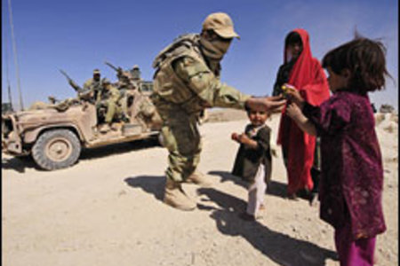 A soldier from the Special Operations Task Group gives sweets to Afghan children in a small village outside Tarin Kowt, Afghanistan. Photo: LS Paul Berry